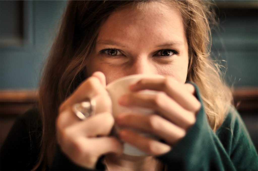 a girl drinking coffee made from coffee beans
